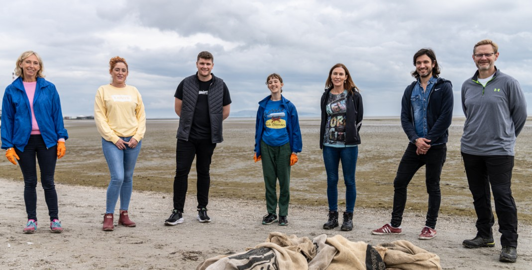 Mount Charles team members stand in a line on Sandymount Beach in Dublin with material bags of litter in front of the group
